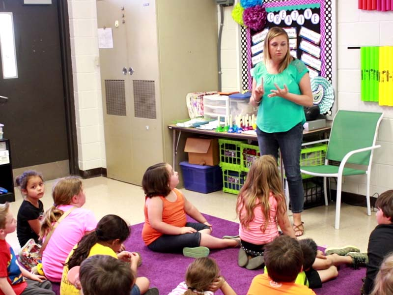 teacher teaching her students in the classroom