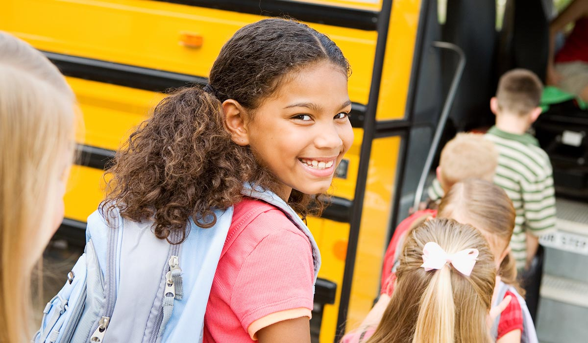 a student smiling as she is walking towards the school bus